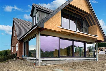 Large Internorm sliding doors on a two-storey extension home with a view